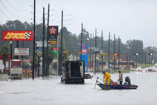Rescuers in a boat move down a street covered in floodwaters from Hurricane Harvey in The Woodlands, Texas. Photo: Bloomberg