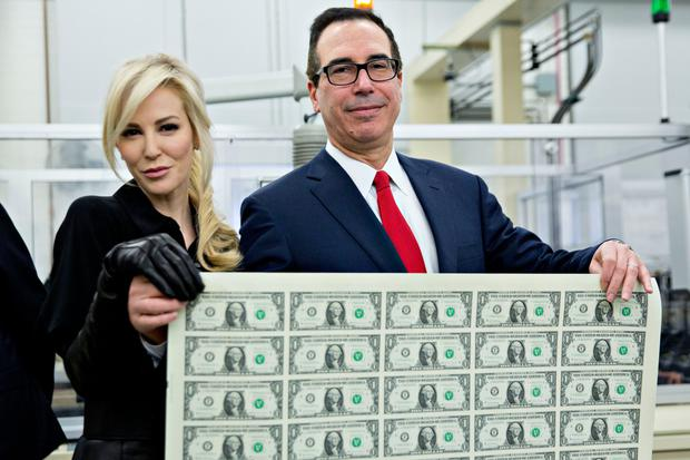 US Treasury Secretary Steven Mnuchin and wife Louise Linton hold an uncut sheet of new dollar notes as boss Donald Trump has succeeded in pushing his revamp of the tax system through Congress