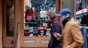 Pedestrians pass in front of a Levi Strauss & Co shop in the SoHo neighbourhood of New York