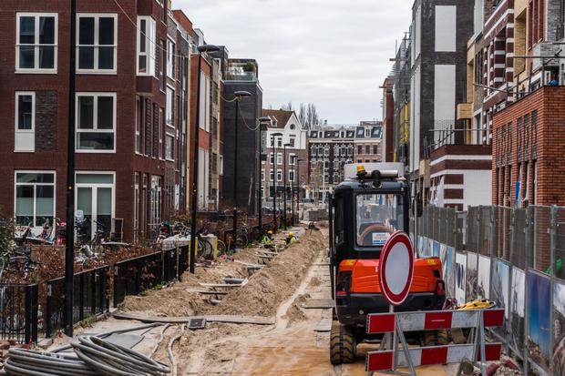 Construction workers install pipes outside a new residential property in Houthaven, Amsterdam. Photo: Bloomberg