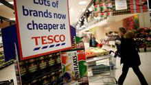 "A customer pushes a shopping cart past a poster reading ""Lots of brands now cheaper at Tesco"" inside a Tesco supermarket store, operated by Tesco Plc, in the Kensington district of London, U.K., on Thursday, Jan. 8, 2015. Photographer: Simon Dawson/Bloomberg"