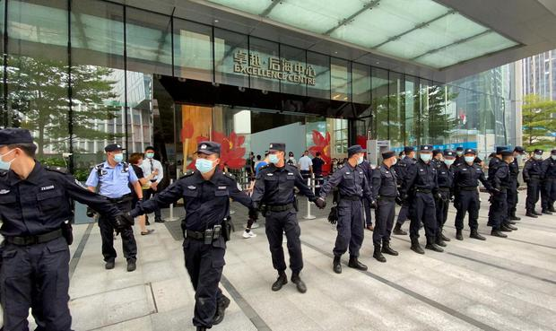 FILE PHOTO: Security personnel form a human chain as they guard outside the Evergrande's headquarters, where people gathered to demand repayment of loans and financial products, in Shenzhen, Guangdong province, China September 13, 2021. REUTERS/David Kirton/File Photo