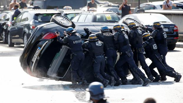 French riot police push an overturned car as striking French taxi drivers demonstrate at the Porte Maillot to block the traffic on the Paris ring road during a national protest against car-sharing service Uber, in Paris, France, June 25, 2015. French taxi