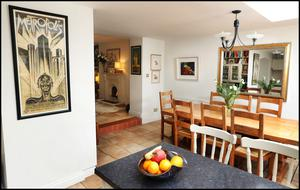 The modern kitchen complete with island is at garden level, and is very bright as it has a skylight and French doors opening on to the garden. Off it is a cosy sitting room, the walls of which are covered in paintings