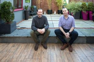 Brian (left) and Shane in their garden. The wood-effect tiles are continued from indoors to the outside, while the building on the left of the photo is the former garage, now the utility room