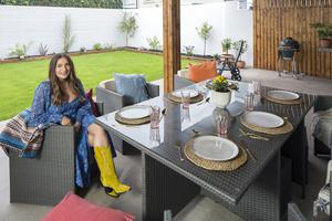 "Courtney in her outdoor deck area, which is practically an extra room as it's roofed and panelled. ""Our carpenter, Gavin Hughes, was great. He suggested the panels. He used cheap pine, but made it look great with the burnt wood effect,"" she says"