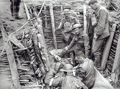 Irish Guards in Wytschaete, Belgium, during World War I with a wounded man in trench. Father Browne Collection
