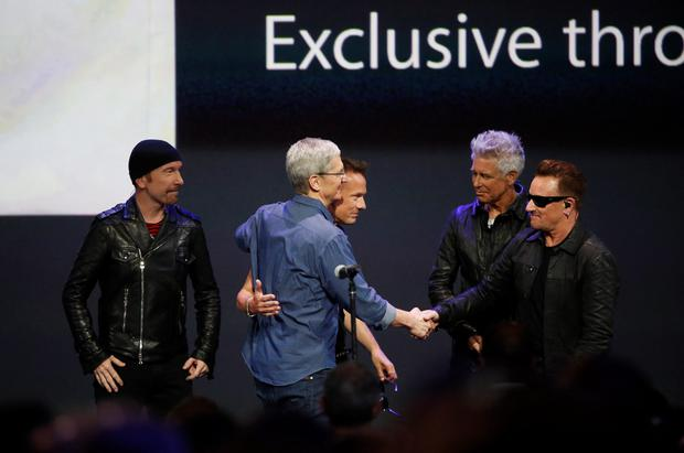 Fruit of their labour: U2 were greeted on stage by Apple CEO Tim Cook after playing at this week's launch of the new iPhone