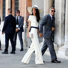 Amal Alamuddin, in a cream Stella McCartney suit, pictured with George Clooney.
