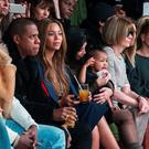 Kim Kardashian attempts to calm her daughter, North, while sitting next to Sean Combs (L), Jay-Z (2nd L), Beyonce (3rd L) and Anna Wintour (2nd R) as they watch a presentation of Kanye West's Fall/Winter 2015 partnership with Adidas at New York Fashion Week