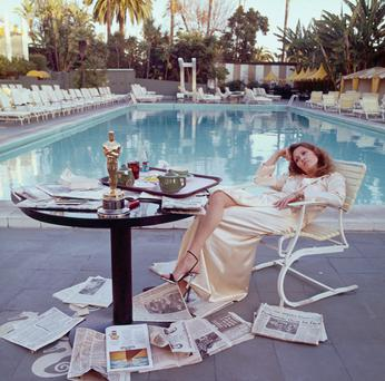 Actress Faye Dunaway takes breakfast by the pool with the day's newspapers at the Beverley Hills Hotel, in March, 1977, the morning after she won the Oscar for Best Actress in a Leading Role for 'Network'. Photo: Terry O'Neill/Getty Images.