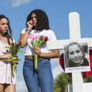 Tatana Hobson 14, Annia Hobson 13, and Leilany Canate, 16, mourn in front of Marjory Stoneman Douglas High School in Parkland (Matias J. Ocner/Miami Herald via AP)