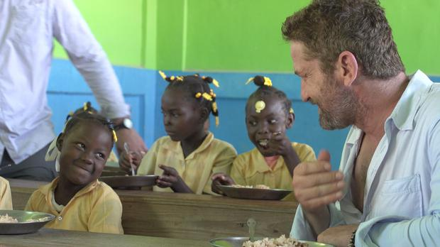 Gerard Butler shares a meal with children in Haiti (Mary's Meals/PA)