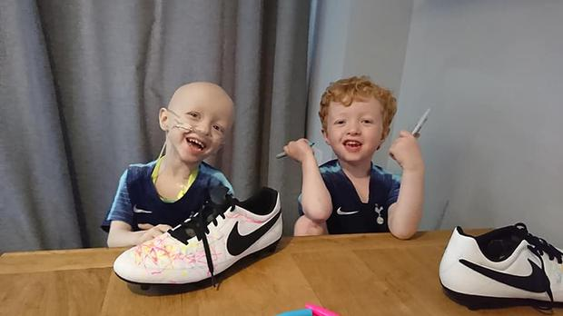 Archie Wilks colouring in his dad's football boots with twin brother Henry (Family handout/PA)