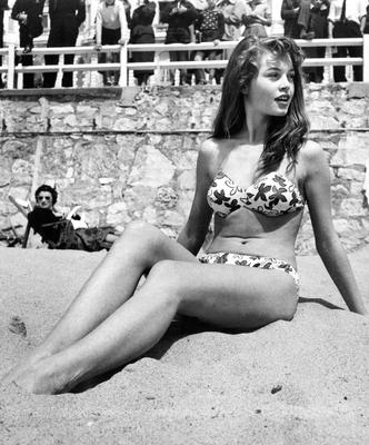 Stunt woman: Brigitte Bardot strikes a pose on the sand in Cannes in 1953