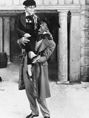Alastair Sim as Ebenezer Scrooge holds up Tiny Tim (Glyn Dearman) on Christmas morning in Brian Desmond Hurst's 1951 adaptation of A Christmas Carol