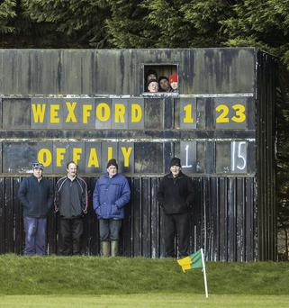 Spectators watch from the scoreboard as Wexford beat Offaly in Blackwater last January in an image from the book. (SPORTSFILE)
