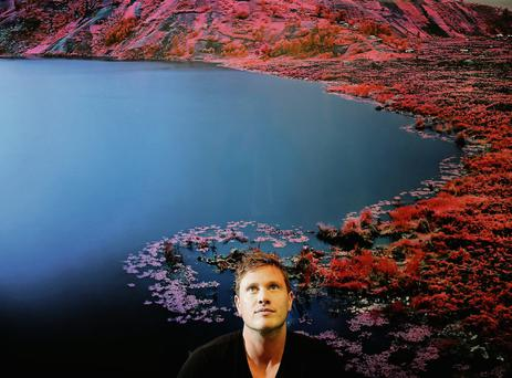 Richard Mosse appears against the striking backdrop of a Congolese lake