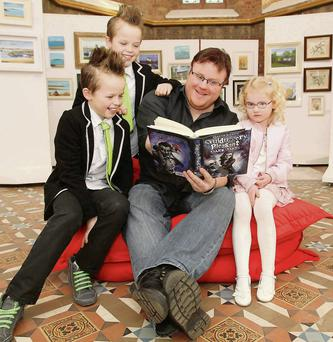Derek Landy reads to twins Arron and Robert Lynch (9) and Mia Creighton (4),in Rush Library