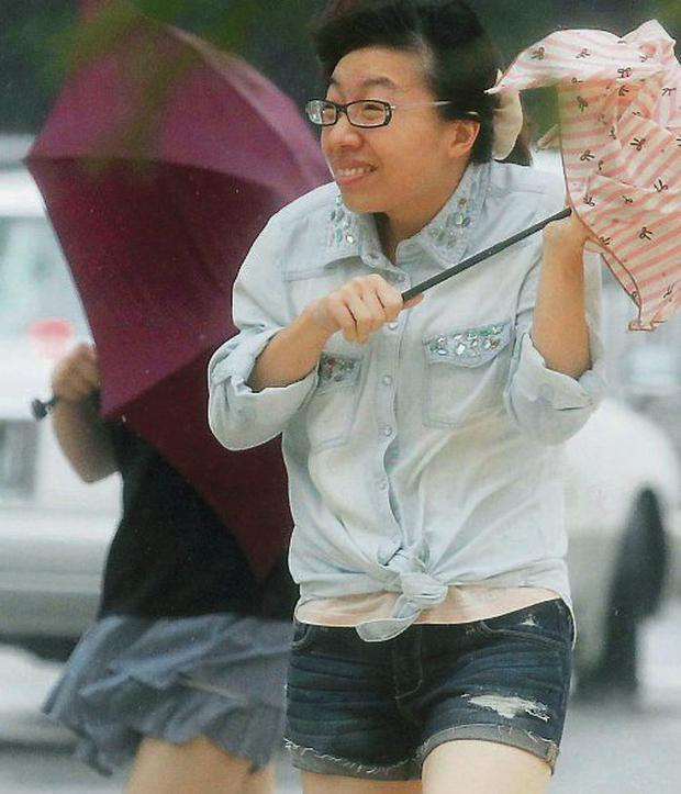 A woman holding an umbrella walks against strong winds and heavy rain brought about by Typhoon Neoguri