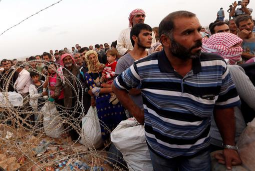 Mass movement: Syrian refugees queue to cross the border into Turkey