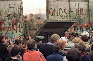 West Berliners crowd in front of the Berlin Wall on November 11, 1989 as they watch East German border guards demolishing a section of the wall in order to open a new crossing point between East and West Berlin, near the Potsdamer Square.