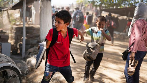 Two little boys: Two young children hold hands as they run away from clashes with Mexican National Guards after their migrant caravan crossed on foot from Guatemala to Mexico last week