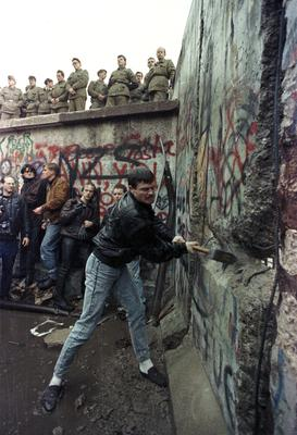 A demonstrator pounds away the Berlin Wall as East Berlin border guards look on from above the Brandeburg Gate on November 11, 1989.