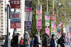Polarised debate: Dubliners walk past campaign posters before the referendum to repeal the Eighth Amendment