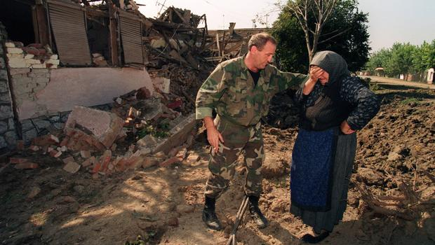 Conflict: A Croatian National Guardsman comforts an old woman on September 26, 1991, outside her home which was destroyed in an air raid during the night by Yugoslav forces.