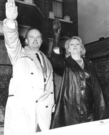 Leader of the Nationalist Socialist Movement Colin Jordan and his wife Francoise Dior giving the Nazi salute to photographers following his speech at the Town Hall in 1965. Photo by Jim Gray/Keystone/Getty Images