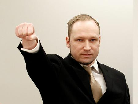 Anders Behring Breivik clenching his fist as he arrives at the courtroom for the first day of his trial in Oslo