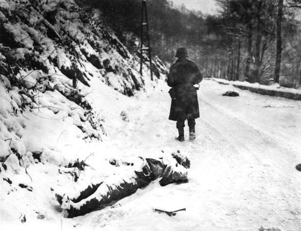 Savagery of war: A dead German soldier covered in snow on the road to the town of La Roche in Ardennes