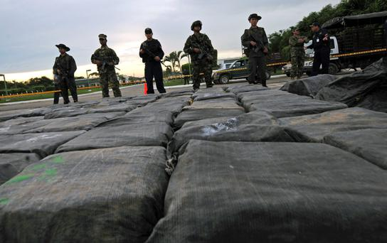 Powder power: Colombian antidrug policemen guard packages containing two tonnes of cocaine after a drug seizure. Photo: Rodrigo Arangua/AFP/Getty Images