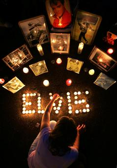 Worshipping the King: a girl lights candles during Elvis Week at Graceland in Memphis, Tennessee. Photo: Getty