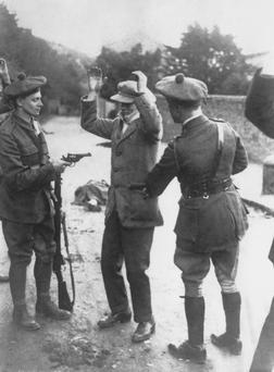 A suspected member of the Irish nationalist party Sinn Fein is searched at gunpoint by temporary constables of the British Black and Tans, during the Irish War of Independence in November 1920