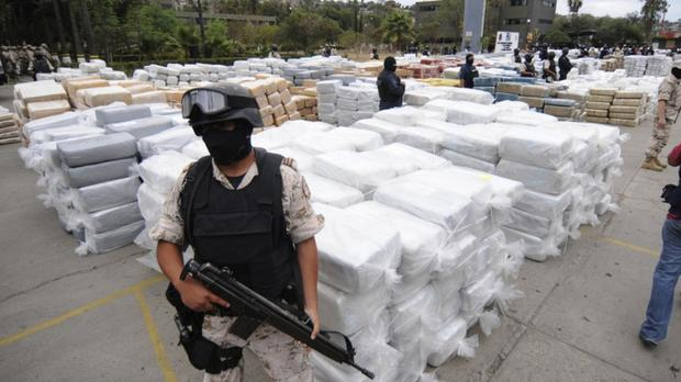 Seized: Mexican police guard a major haul of marijuana. Last year, 33,000 people were killed in gang-related murders fuelled by drug trafficking in the Central American country
