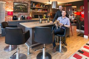 Brian Gorry (standing) and Shane Kirby in their extended kitchen with Minnie.The units are from Kube, and they bought the chairs for a fraction of their usual retail price  from a hair salon which was closing down. The builders recycled their old units by fitting them in the outdoor utility room