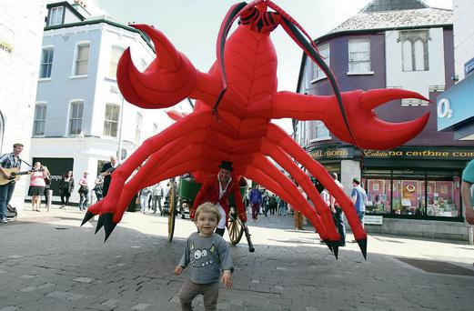 Ludwik Seamus is chased by a giant inflatable lobster at launch of the Galway International Arts Festival