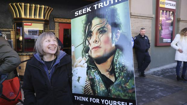 Brenda Jenkyns who drove from Calgary, Canada stands with a sign outside of the premiere of the Leaving Neverland Michael Jackson documentary (Danny Moloshok/Invision/AP)