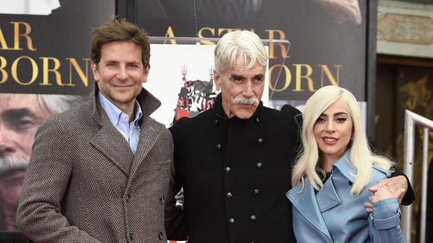 Bradley Cooper, left, and Lady Gaga, right, pose with actor Sam Elliott during a hand and footprint ceremony honouring Elliott (Chris Pizzello/Invision/AP)