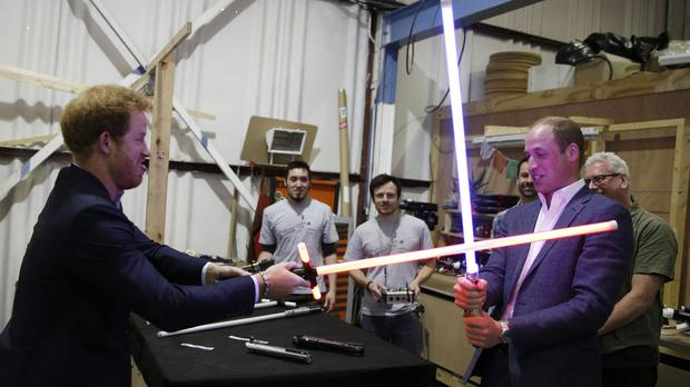 Prince Harry and the Duke of Cambridge try out lightsabers during a tour of the Star Wars sets at Pinewood studios