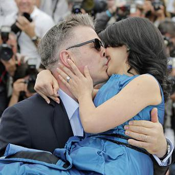 Alec Baldwin carries and kisses his pregnant wife Hilaria Thomas on the red carpet at Cannes