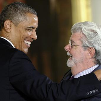 President Barack Obama hugs director George Lucas before presenting him with the National Medal of Arts