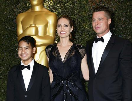 Suits you: Brad Pitt, with Angelina Jolie and Maddox Jolie-Pitt, has probably gotten tips off George Clooney.