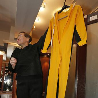 Anna Lee, vice-chairman of Spink auction house, holds Bruce Lee's original yellow jumpsuit