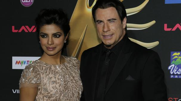 John Travolta poses with Indian film star Priyanka Chopra at the International Indian Film Awards