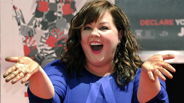 Melissa McCarthy shows off her hands after putting them in cement during a ceremony in Hollywood