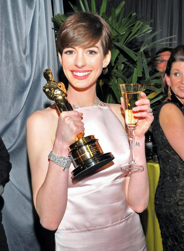 Anne Hathaway poses with her award for best actress in a supporting role for