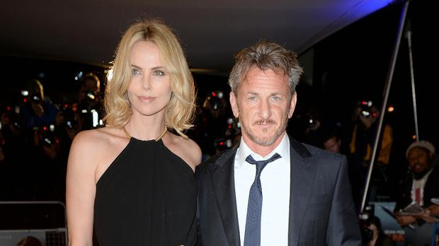 Sean Penn (right) and partner Charlize Theron attend the World Premiere of The Gunman (PA Wire)